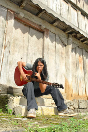hushing: Asian exotic long haired teenager sitting in front of an old wooden building with an acoustic guitar, hushing and asking for silence.