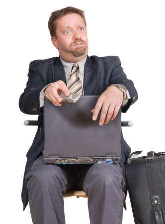 travelling salesman: Travelling businessman or salesman with laptop and cell phone sitting bewildered after a phone call with a perplexed expression on his face. Isolated over white. Stock Photo
