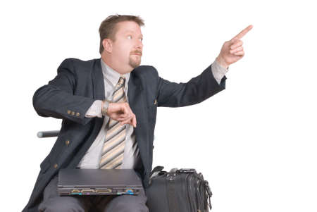 rushed: Travelling businessman in a waiting shed on an airport or train station with luggage and laptop PC, rushed and on a tight schedule with wristwatch up, pointing with his finger in the distance. Isolated over white with copy space.