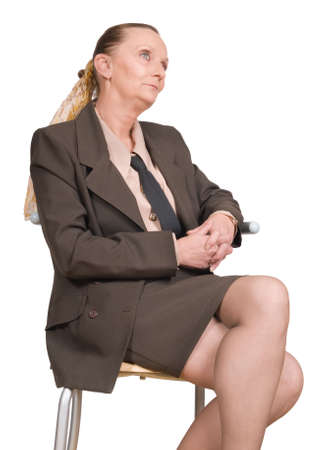 crossed fingers: Lonely female senior artistic manager pondering and thinking while sitting on a chair, fingers crossed and staring into the void. Isolated over white. Stock Photo