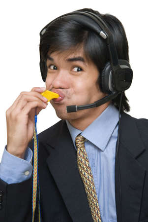 raised eyebrow: Closeup portrait of young Asian call or help center agent with headset blowing a whistle with a cheesy naughty smile. Isolated over white. Stock Photo