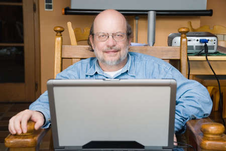 Senior mature bald multimedia professor with glasses smiling gently and sitting in an armchair in his campus lab or library preparing his course on a laptop PC.