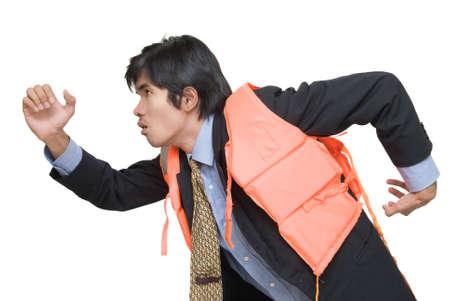 imminent: Young Asian executive or corporate businessman in suit, necktie and life vest running and rushing to escape imminent financial or business danger. Side view, isolated over white. Stock Photo