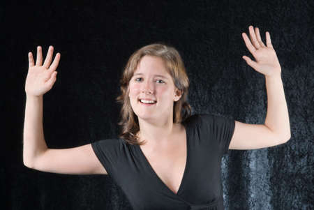 extrovert: Cheering elated and laughing classy glamor girl with hands up in a fancy fashionable evening gown. Stock Photo