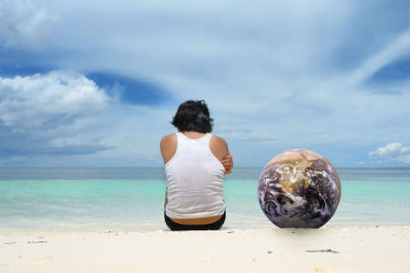 Asian young man sitting alone next to a globe on a tropical beach and staring over the sea under a majestic cloudscape. Back view with copy space in the sky. Globe courtesy NASAJPL. photo
