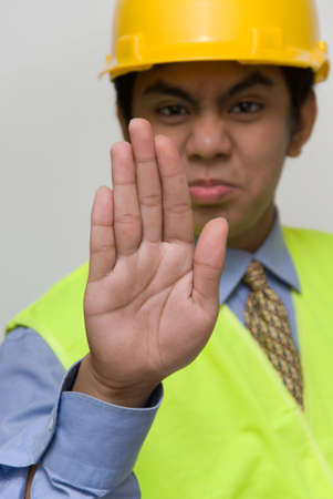 Stop, halt or no entry hand sign, flat hand extended in focus, by a young Indian stern looking foreman, engineer or contractor. photo
