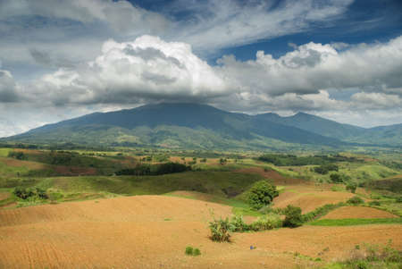 Plowed field with rich fertile soil on a volcanic tropical plateau in front of a mountain covered with rain forest and topped by a majestic cloudscape with nimbus clouds around mountain top in Bukidnon (Mindanao, Philippines). Stock Photo