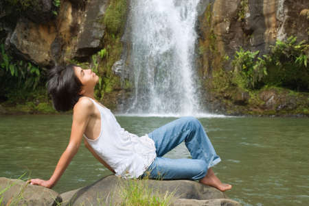Asian teenage boy laying relaxed in front of a tropical waterfall and enjoying the tropical scenery and the sun. photo