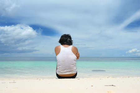 absent: Asian young man sitting alone on a tropical beach and staring over the sea under a majestic cloudscape. Back view with copy space in the sky.