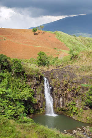 mountainous: Tropical wild landscape on the Bukidnon (Mindanao, Philippines) volcanic mountainous plateau with red fertile volcanic soil, jungle, canyons and a secluded waterfall. Stock Photo