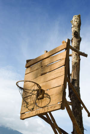 backboard: Homemade vintage backboard of wood planks with rusted nails and rusted basket for basketball play in a poor rural Western village.