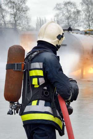 消防士ヘルメットと酸素タンク タンクの消火の防護服でホースで火し、水の産業場所でジェット。背面図。