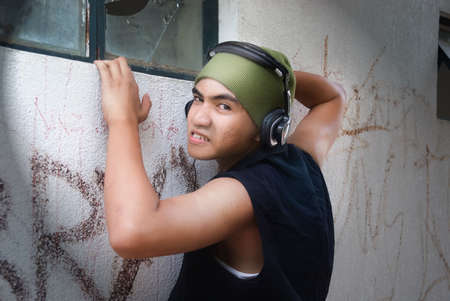 Young Hispanic burglar with headphones and angry expression caught red-handed at night in bright spotlight intending to enter building by broken window.