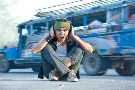 noisy: Young Hispanic rapper dude in casual grunge clothing with cap and headphone sitting on the street midst jeepney traffic covering his ears for sound or noise overload, shouting with an intense expression of disgust on his face. Stock Photo