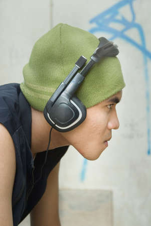 Closeup side view or profile portrait of tough young grunge Hispanic urban rapper dude with cap and headphone against a wall with graffiti. Stock Photo