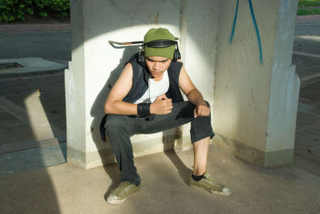 Young Hispanic male rapper with cap and headphones sitting in a sunny spotlight, in a wasted urban environment vandalized with graffiti.