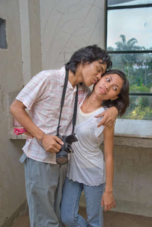 suitor: Two teenage lovers of mixed ethnicity embracing, standing and kissing in an urban wasted environment with graffiti on the walls, boy suitor holding camera, courting slightly reserved girl.