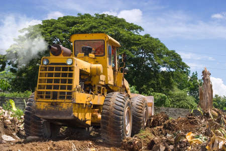 A worn, rusted and recycled polluting bulldozer with smoke plume clearing plant debris and soil preparing and leveling a tropical terrain with a large tree in the background. Stock Photo