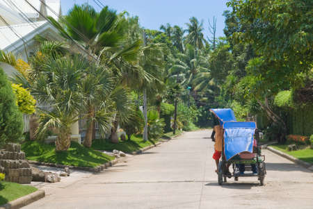 Street view of an affluent tropical lush Asian suburb or compound with greens and a pedicab or tricycle carrying passenger. Stock Photo - 6991724