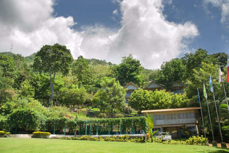 ecovillage: Tropical Asian resort with lush gardens, lodging, exotic trees and rain forest around a lawn in the mountains under a majestic cloudscape. Malasag Ecovillage, Cagayan de Oro, Philippines.