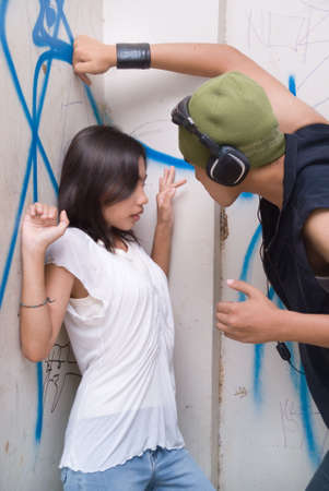 gang: Young tough Hispanic grunge gangsta mugger with headphone and cap intimidating a cornered and frightened girl in an urban slum with graffiti on the wall. Stock Photo