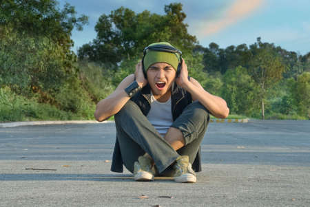 Young Hispanic rapper dude in casual grunge clothing with cap and headphone sitting in the middle of a green suburban street covering his ears for sound or noise overload, shouting with an intense expression of disgust on his face. Zdjęcie Seryjne