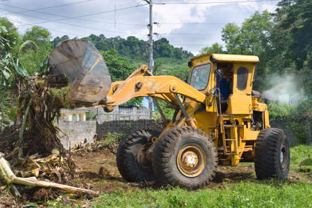 leveling: A worn, recycled bulldozer with polluting smoke plume clearing plant debris and soil Stock Photo