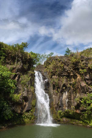 Secluded jungle waterfall in a volcanic sediment canyon on the tropical Bukidnon plateau, Mindanao, Philippines, topped by a majestic cloudscape.