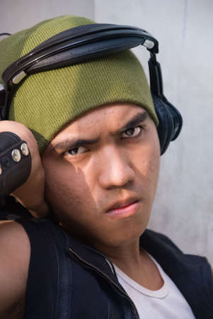 pimples: Closeup portrait of young Asian male rapper with pockmarked face, looking tough, with headset and cap with strong contrast. Stock Photo