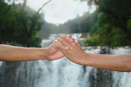 団結と環境と惑星を保存する共通した決意を象徴するジャングルと熱帯の滝の前で握手。