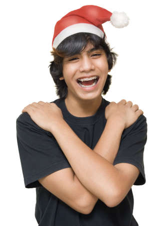 Portrait of Indian male teenager with arms crossed on shoulders, with teeth braces and Santa Claus hat laughing loud. Isolated over white.