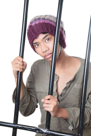 Asian male teenager with cap and grunge shirt holding and standing behind prison bars, looking wondering and innocently at cam. Isolated over white. photo