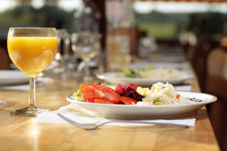 food table: Food table set for simple lunch in a cozy country inn dinner hall with orange juice glass and dish with fresh tomatoes and rice.