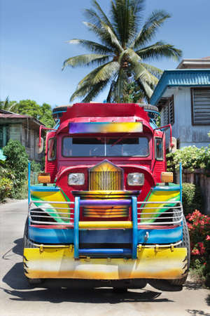 Frontal view of a Filipino colorful rural jeepney (public transport, bus) parked in a small Mindanao town.