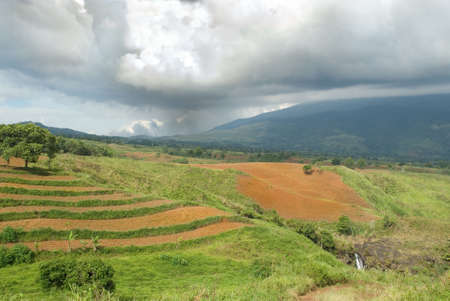 Tropical agriculture landscape with plowed fields under a low nimbus cloudscape on the Bukidnon (Mindanao, Philippines) volcanic mountainous plateau with red fertile volcanic soil, jungle and canyons. Stock Photo - 6172758