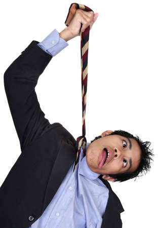 sacked: Young Asian businessman in suit hanging himself by his necktie as a final extreme reaction to failure, bankruptcy, being sacked or fired, or to the economy crisis. Isolated over white. Stock Photo