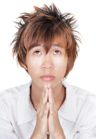 imploring: Closeup portrait of angelic emo Korean teenager with orange dyed hair, looking up sadly and solemnly and begging with hands praying. Isolated over white.