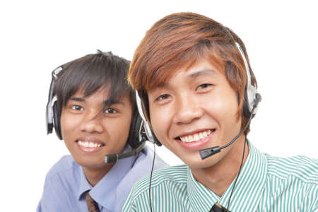 Two Asian call center agents or customer care representatives with headset at work listening and smiling friendly radiating trust and professionalism. Isolated over white. photo