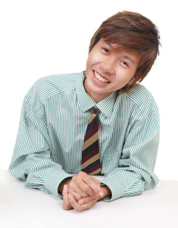 Friendly smiling young Asian or Korean businessman, salesman or consultant, sitting at his desk and leaning over like convincing a customer. Isolated over white. photo