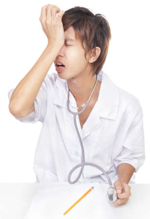 Young Korean doctor sitting on desk banging his head, realizing a mistake, a malpractice or something he overlooked or forgot. Isolated over white. photo