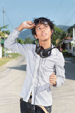 Asian male teenager in fashionable outfit looking at the sun holding sunshades up on an affluent suburban street.