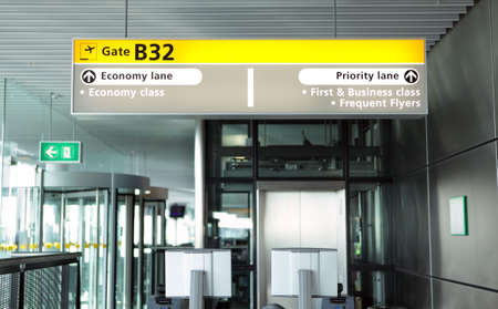 Departure boarding gate inside a modern airport terminal with illuminated head sign indicating lanes for class of passengers and equipment for boarding pass verification.