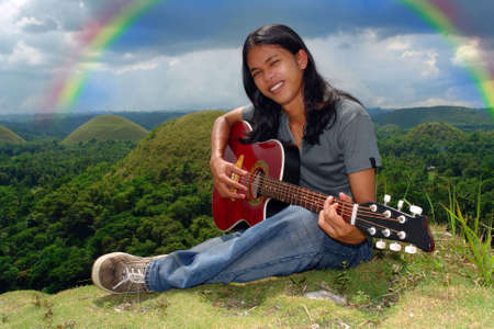 Smiling Asian long haired hippie teenager playing the guitar and sitting outdoors under a rainbow over a tropical hilly landscape.