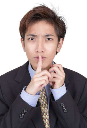 hushing: Portrait of young Chinese businessman hushing with fingers on lips and a mesmerizing urging gaze insisting on discretion about a deal. Isolated over white. Stock Photo