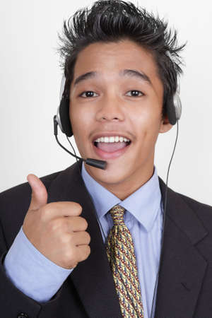 enthusiast: Cheering enthusiast young junior Asian call or help center agent portrait with headset, giving the thumbs up sign. Stock Photo
