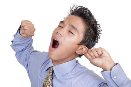 Bored and yawning young junior Asian businessman portrait with eyes closed and fists up, isolated over white.