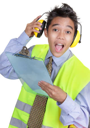 Junior Asian foreman or engineer in protective suit holding clipboard and lifting ear protectors with a surprised attentive facial expression. Isolated over white.