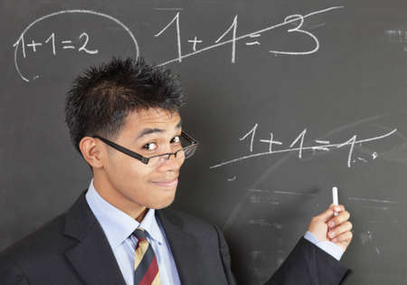 Smirking Asian math teacher with nerd glasses in suit pointing an elementary wrong addition sum written on a blackboard. Zdjęcie Seryjne