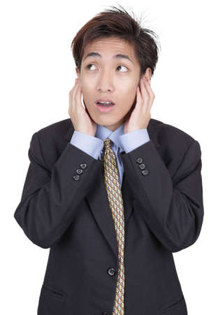 Standing oriental Chinese young businessman covering his ears in denial of reality and deaf for corporate and business facts. Isolated over white. photo