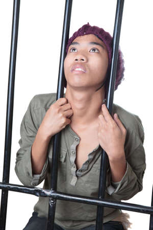 an inmate: Asian male teenager with cap and grunge shirt holding and standing behind prison bars, looking up desperately and gasping. Isolated over white. Stock Photo